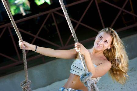 Blonde lady swinging on rope swings on the beach