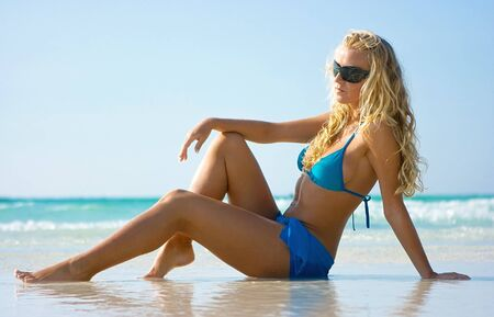 Blonde lady in sunglasses on the sandy beach