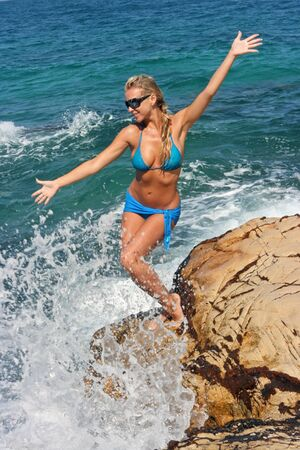 Blonde in sea splashes on the rocky beach Stock Photo
