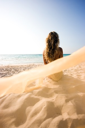 Blonde mermaid sitting on the beach and turned her back Stock Photo