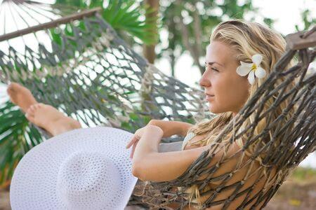 Blonde girl with white flower in hair lying on the hammock photo