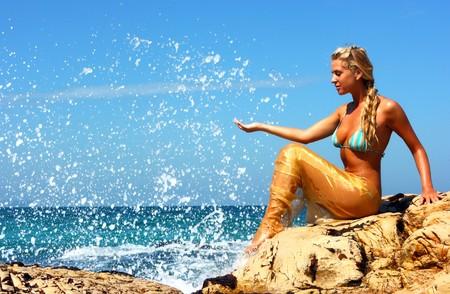 Blonde mermaid sitting on the rocky beach Stock Photo