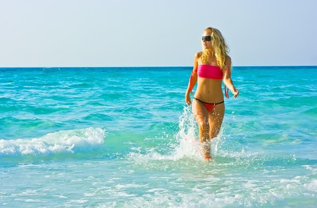 Blonde girl walking out of the surf