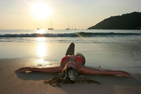 Blonde girl lying on the sand beach