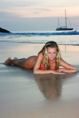 horizont: Blonde girl lying on the sand beach