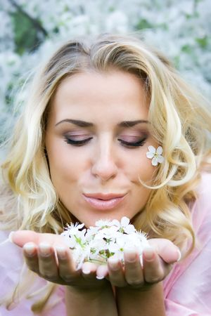 Yound blonde with cherry flowers in hands