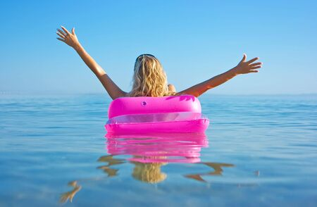 Blonde girl floating on inflatable raft in the sea photo