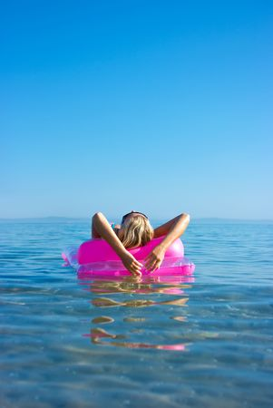 Beautiful blonde girl floating on inflatable raft in the sea