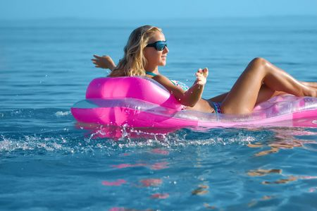 woman floating: Beautiful blonde girl floating on inflatable raft in the sea