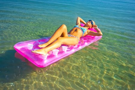Pretty blonde girl floating on inflatable raft photo