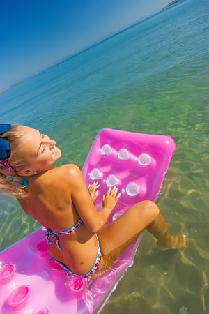 Pretty blonde girl floating on inflatable raft Stock Photo - 5291984