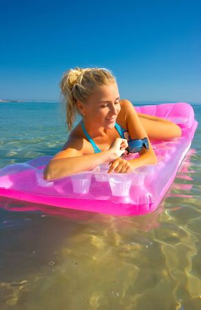 Pretty blonde girl floating on inflatable raft Stock Photo - 5291985