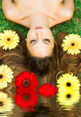 Brunette girl lying on the glass with flowers and reflection in water Stock Photo - 5305575