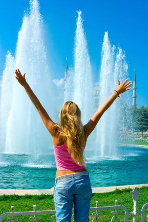 Blonde girl standing in front of the fountain