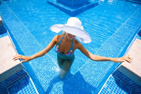 Girl in white hat in the swimming pool Stock Photo