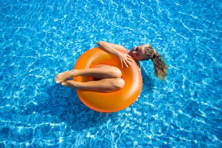 Beautiful blonde girl swimming in hotel pool on inflatable raft Stock Photo - 5738219
