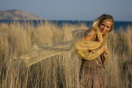 Good looking young blonde model girl with long hair standing in the autumn beads field with transparent shawl in hands Stock Photo - 5738222