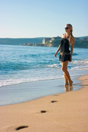 Beautiful blonde girl standing on the sand beach with footprints on it