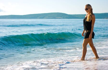 Beautiful blonde girl standing on the sand beach Stock Photo - 5791188