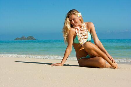 Blonde girl with tropical flowers on Hawaii sand beach