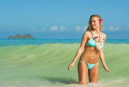 Young blonde girl with slim figure standing in the sea