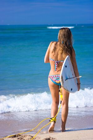 Blonde girl surfer with board in front of the sea photo
