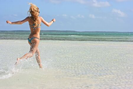 Blonde girl running in the water on the beach