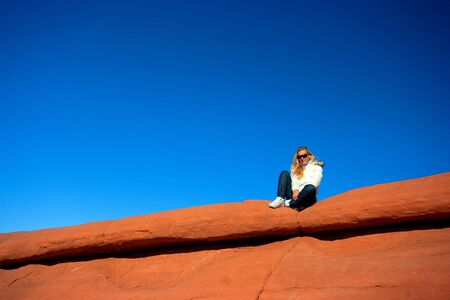 Girl in sunglasses sitting on the slope of the red mountain