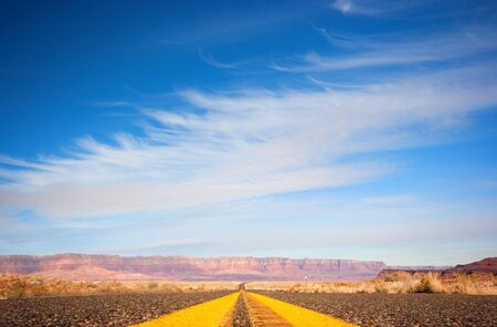 Asphalt road from low angle with mountains on background