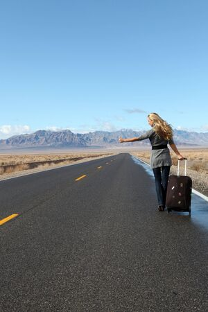 Blonde model walking along the road with suitcase