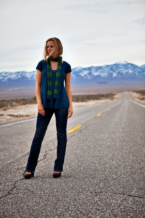 Blonde model standing on an empty road photo