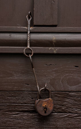 circumspect: Old wooden door with Chain key lock.