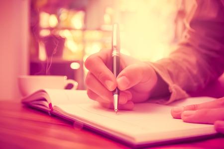 persona escribiendo: La mano del hombre la celebración de una pluma de escribir en el cuaderno.