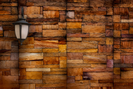 The lamp on the wall made of stone blocks.