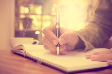 Man hand holding a pen writing on the notebook, Vintage style. Standard-Bild