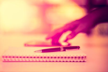 배경 흐림 효과와 노트북에 검은 펜 남자는 모바일 응용 프로그램, 빈티지 스타일을 사용하고 있습니다. 스톡 콘텐츠