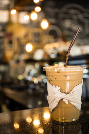 Iced coffee is placed on the counter of a coffee bar, a blurred backdrop of coffee maker and accessories. Standard-Bild
