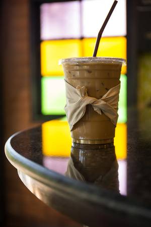 Iced coffee is placed on the bar counter of the cafe, with light from the stained glass behind the cup.