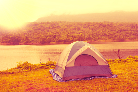 The tent on the grass, backdrop is the view reservoir, hills, forests and fog of the mountain, Vintage style. 스톡 콘텐츠