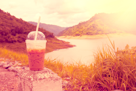 Cool coffee in plastic cups, with backdrop views as reservoirs, forests, and mountains, vintage style.