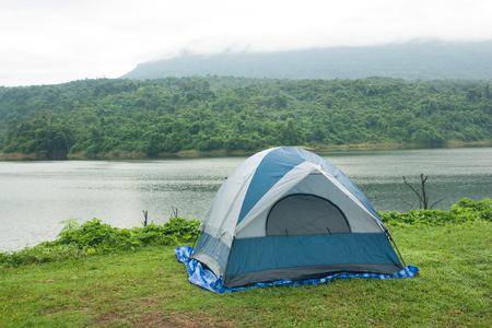 Tent on the grass, with backdrops are reservoirs, forests, mountains and fog, morning.