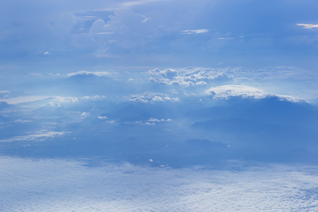 Natural sky and clouds background, Cloudy cover over mountains, by the window of plane.