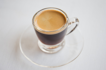 Espresso coffee in glass cup, on a white background.