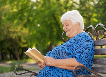 Senior woman reads the book sitting on a bench Stock Photo - 18768174