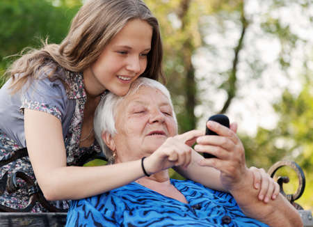 grandchilds help the grandmother to master the smart phone