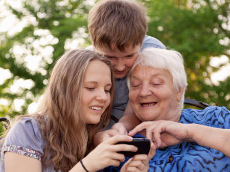 grandchilds help the grandmother to master the smart phone  photo