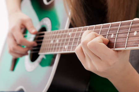 girl playing guitar: The girl plays a guitar, close-up