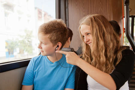 the occupant:  girl and  boy go in the bus and look out of the window Stock Photo