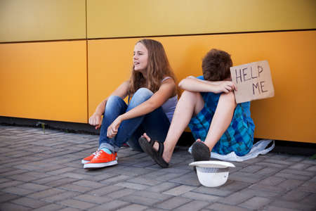 homeless children: Homeless teenage boy and girl begging in street (The production scene; problem-free children play a role of beggars)