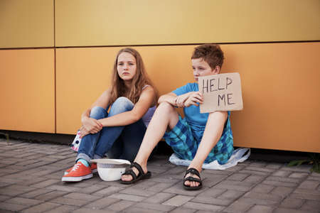 role play: Homeless teenage boy and girl begging in street (The production scene; problem-free children play a role of beggars)